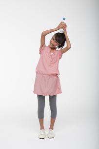 ペットボトルを頭上に持って笑顔で立つ女の子の写真素材 [FYI04068078]