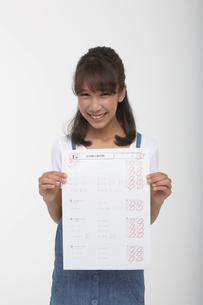 百点のテストのプリントを持つ笑顔の女の子の写真素材 [FYI04068079]