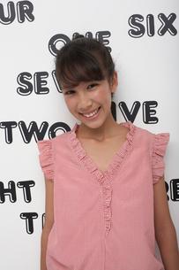 英単語を貼った壁の前に立つ笑顔の女の子の写真素材 [FYI04068090]