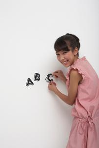 白い壁にアルファベットのシールを貼る笑顔の女の子の写真素材 [FYI04068092]