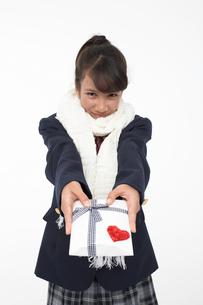 プレゼントを差し出すマフラーをした女子学生の写真素材 [FYI04068098]