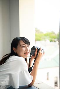 一眼レフカメラを構えて笑っている女性の写真素材 [FYI04068133]