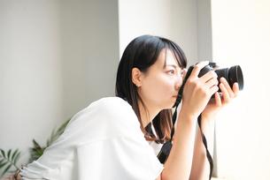一眼レフカメラで写真を撮影している女性の写真素材 [FYI04068520]