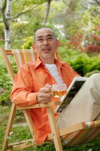 庭でくつろぐシニア男性の写真素材 [FYI04069548]
