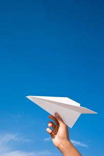 紙飛行機を飛ばそうとしている手の写真素材 [FYI04069594]