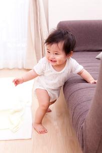 ソファーにつかまって立つ赤ちゃんの写真素材 [FYI04069729]