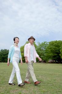 公園を散歩するシニア夫婦の写真素材 [FYI04069744]