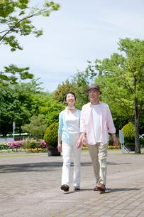 公園を散歩するシニア夫婦の写真素材 [FYI04069752]