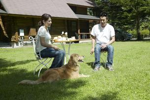 芝生でティータイムを楽しむカップルと犬の写真素材 [FYI04070195]