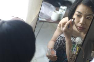鏡を見て化粧をする女性の写真素材 [FYI04070260]
