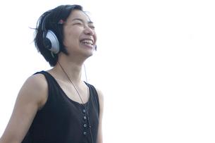 ヘッドフォンをして笑う女性の写真素材 [FYI04070261]