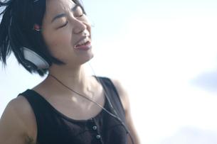 ヘッドフォンをして歌う女性の写真素材 [FYI04070265]