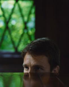 机越しに覗いている外国人男性の写真素材 [FYI04070271]