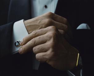 タキシード姿の外国人男性がカフスを直す手の写真素材 [FYI04070276]