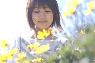 花の前でうつむく女性の写真素材 [FYI04070284]