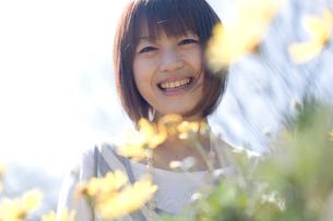 花越しに微笑む女性の写真素材 [FYI04070289]