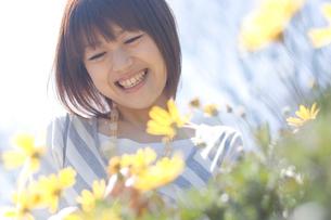 花の前で笑う女性の写真素材 [FYI04070295]