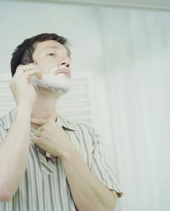 鏡に向かいシェービングする外国人男性の写真素材 [FYI04070308]
