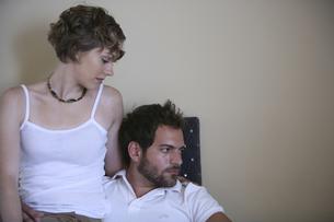 椅子に座って寄り添う男性と女性の写真素材 [FYI04070324]