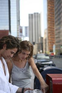 路上で新聞を読む男性と女性の写真素材 [FYI04070341]