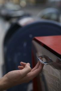 新聞スタンドを開ける男性の手の写真素材 [FYI04070343]