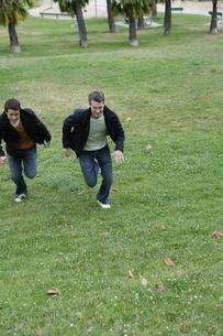 芝生を走る男性2人の写真素材 [FYI04070350]