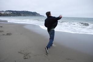 海に石を投げる男性の写真素材 [FYI04070351]