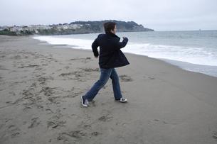 海に石を投げる男性の写真素材 [FYI04070352]