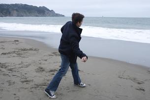 海に石を投げる男性の写真素材 [FYI04070353]