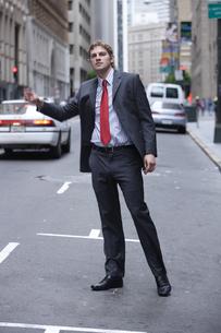 タクシーを拾おうとするビジネスマンの写真素材 [FYI04070360]
