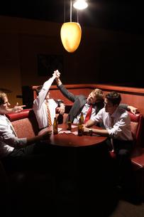 バーのテーブルでビールを飲む男性4人の写真素材 [FYI04070365]