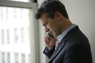 携帯電話で話すビジネスマンの写真素材 [FYI04070388]