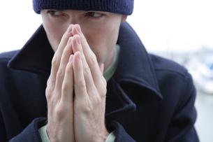 寒そうに手を温める男性の写真素材 [FYI04070389]