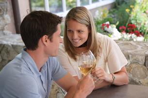庭のテーブルでワインを飲むカップルの写真素材 [FYI04070412]