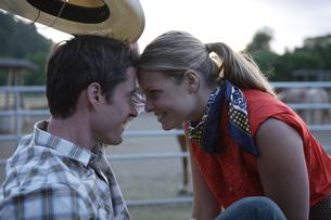 カウボーイハットをかぶり顔を寄せ合うカップルの写真素材 [FYI04070436]