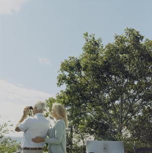 双眼鏡で景色を眺める男性と寄り添う女性の写真素材 [FYI04070443]
