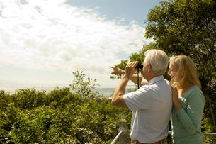 双眼鏡で景色を眺める男性と寄り添う女性の写真素材 [FYI04070444]