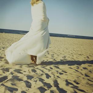 ブランケットを羽織って海岸を歩く女性の写真素材 [FYI04070450]