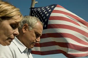 アメリカ国旗の前で祈りを捧げる夫婦の写真素材 [FYI04070467]