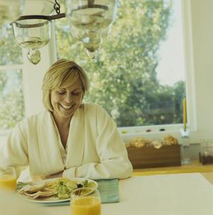ガウンを着て朝食を食べる女性の写真素材 [FYI04070469]
