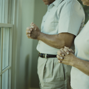 窓際で祈りを捧げる夫婦の写真素材 [FYI04070470]