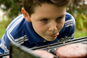 バーベキューグリルの前で舌を出す少年の写真素材 [FYI04070510]