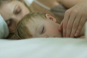 ベッドで寝ている男の子と母親の写真素材 [FYI04070515]