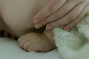 ベッドで寝ている男の子と母親の手の写真素材 [FYI04070517]