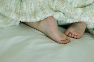 ベッドで寝ている男の子の足の写真素材 [FYI04070518]