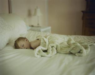 ベッドでうつぶせに寝ている男の子の写真素材 [FYI04070523]