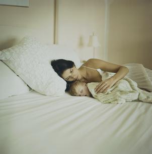 ベッドで寝ている男の子と母親の写真素材 [FYI04070526]