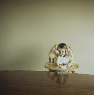 ベビーチェアに座って食事をする女の子の写真素材 [FYI04070535]