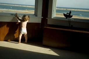 窓辺から外を見ようとしている男の子の写真素材 [FYI04070572]