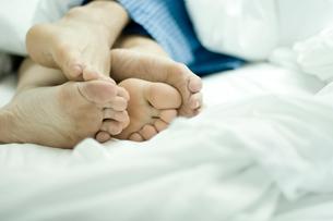 ベッドで寄り添って寝ているカップルの足の写真素材 [FYI04070577]